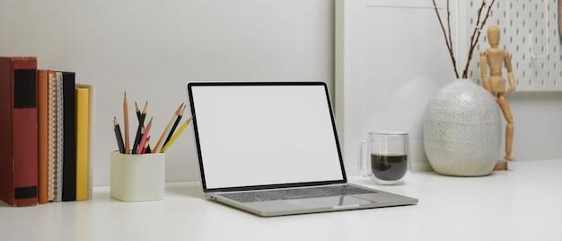 Moderner schreibtisch mit laptop, schreibwaren, büchern, kaffeetasse und dekorationen