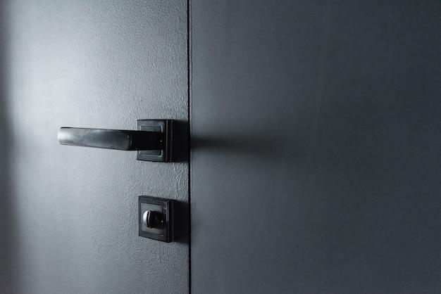 Moderner schwarzer türgriff und schloss auf schwarzer versteckter holztür. nahaufnahmeelemente des modernen innenraums der wohnung.