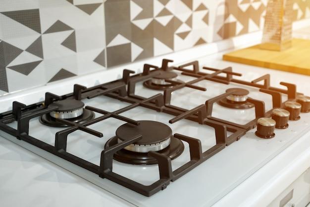 Moderner silberner gasherd aus edelstahl mit schwarzen elementen und brennern auf der oberen ansicht der weißen küchenset-oberfläche