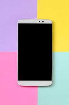 Moderner smartphone mit schwarzem bildschirm onfashion blaues, gelbes, violettes und rosa pastellpapier