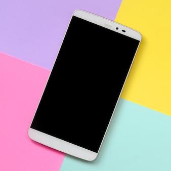 Moderner smartphone mit schwarzem schirm auf bunter beschaffenheit