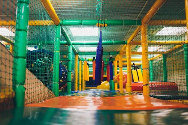 Moderner spielplatz im innenbereich. kinderdschungel in einem spielzimmer. runder tunnel im kindergymnastikraum.