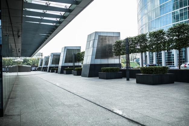 Moderner stadtstraßenfußweg mit glasfensterwand und -sonnenlicht