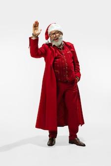 Moderner stilvoller weihnachtsmann im roten modischen anzug lokalisiert auf weißem hintergrund
