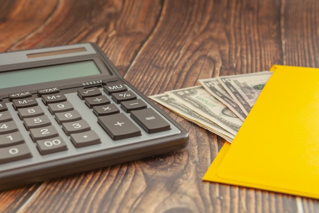 Moderner taschenrechner auf einem holztisch mit einem gelben umschlag und einem geld