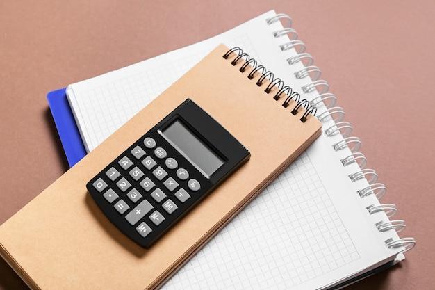 Moderner taschenrechner mit notizbüchern auf farboberfläche