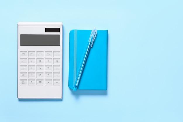 Moderner taschenrechner, stift und notizbuch auf farboberfläche