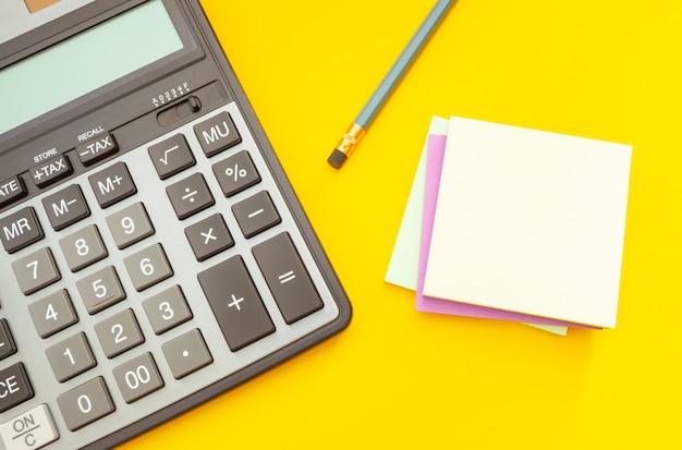 Moderner taschenrechner und bleistift mit aufklebern für anmerkungen