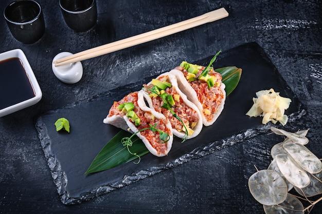 Moderner thunfisch-tartar mit avocado in reischips. gesundes essen. rohe meeresfrüchte. roher thunfisch mit mikrogrün und tobiko-kaviar. schönes essen serviert auf dunklem hintergrund. japanischer essensstil