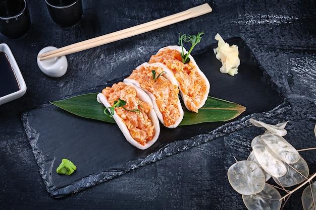 Moderner thunfischlachs mit avocado in reischips. gesundes essen. rohe meeresfrüchte. roher thunfisch mit mikrogrün und tobiko-kaviar. schönes essen serviert auf dunklem hintergrund. japanischer essensstil
