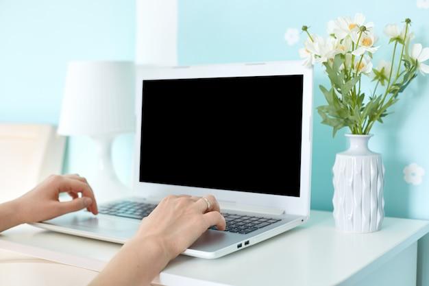 Moderner tragbarer laptop-computer mit leerem bildschirm auf schreibtisch, umgeben von lampe und blumenstrauß auf blauer wand. nicht erkennbare frau arbeitet entfernt an modernen elektronischen geräten, die mit wlan verbunden sind