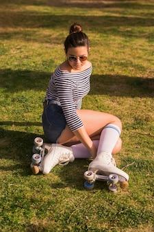 Moderner tragender rollschuh der jungen frau, der auf grünem gras sitzt