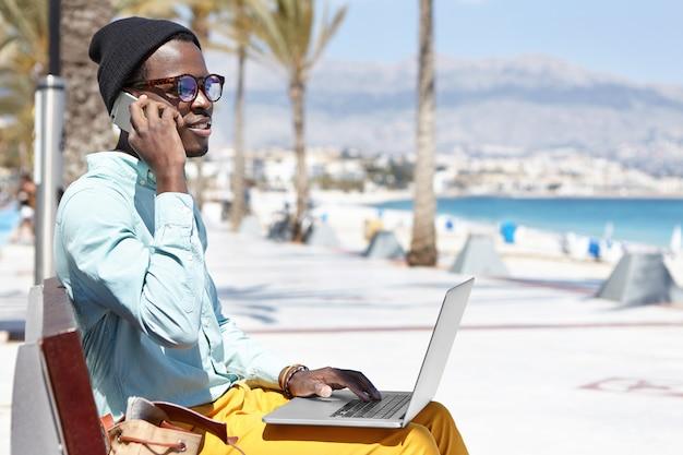 Moderner trendiger aussehender junger dunkelhäutiger geschäftsmann, der entfernt auf laptop-pc arbeitet und handy für geschäftsanrufe beim sitzen auf promenade entlang der blauen küste am sonnigen tag verwendet