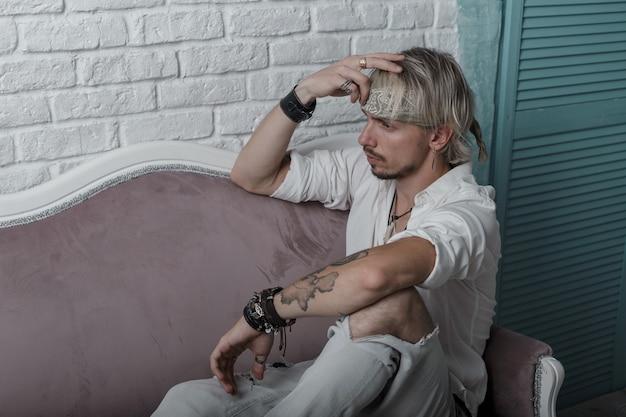 Moderner trendiger junger mann mit einem bart in einem modischen grauen kopftuch mit einer tätowierung in einem stilvollen weißen hemd in zerrissenen jeans, die auf einem vintage-sofa sitzen
