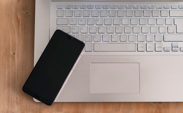 Moderner und designlaptop und schwarzer smartphone in einer hellen hölzernen tabelle