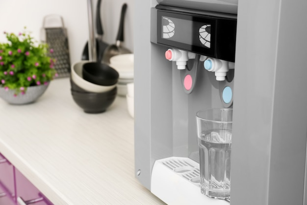 Moderner wasserkühler mit glas auf küchentisch
