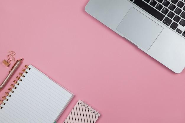 Moderner weiblicher arbeitsraum, draufsicht. laptop, notizbücher, stift in der farbe roségold, klemme auf rosa hintergrund