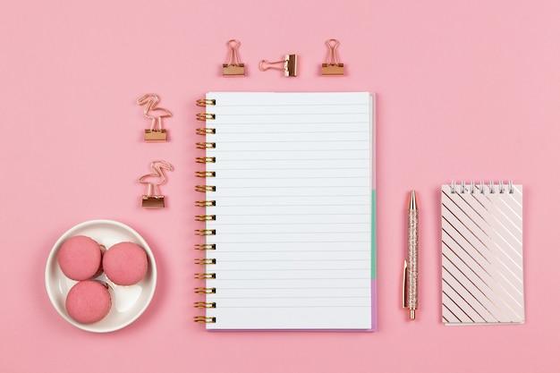 Moderner weiblicher arbeitsraum, draufsicht. notizbücher, stift, klammern auf rosa hintergrund