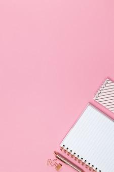 Moderner weiblicher arbeitsraum, draufsicht. notizbücher, stift, klemme auf rosa hintergrund, kopierraum, flache lage.