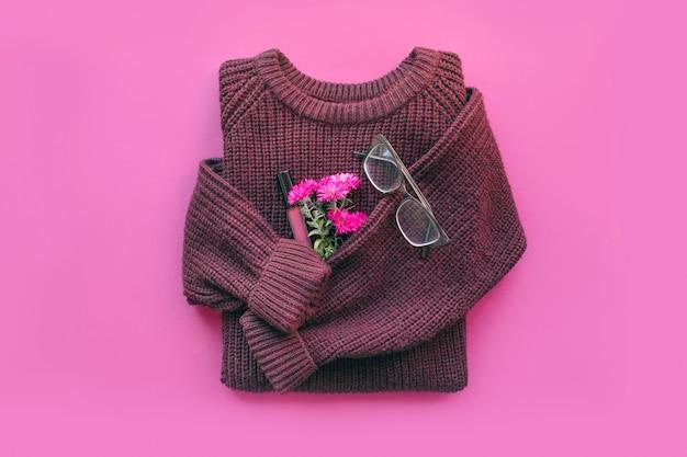 Moderner weiblicher minimaler hintergrund mit gemütlicher burgunder-strickjacke, jeans, blumen, lipgloss