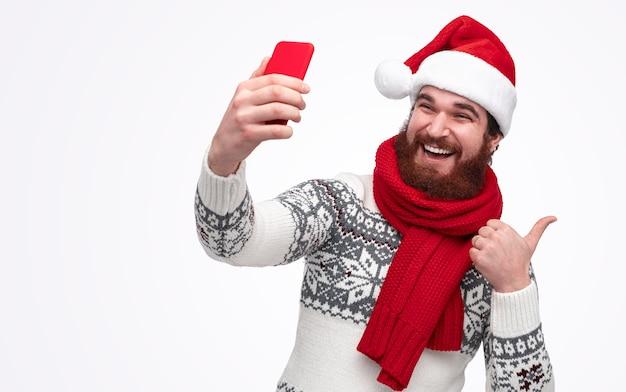 Moderner weihnachtsmann, der ein selfie-bild macht
