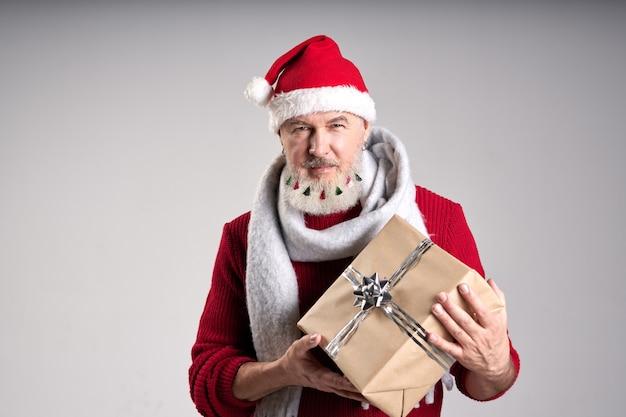 Moderner weihnachtsmann, gutaussehender mann mittleren alters mit verziertem bart, der weihnachtsmütze anschaut