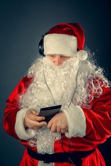 Moderner weihnachtsmann mit kopfhörern, die musik hören