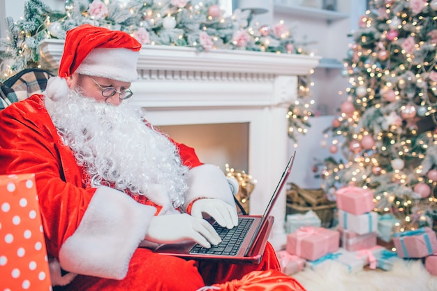 Moderner weihnachtsmann sitzt am kamin und am weihnachtsbaum unter verwendung eines laptops