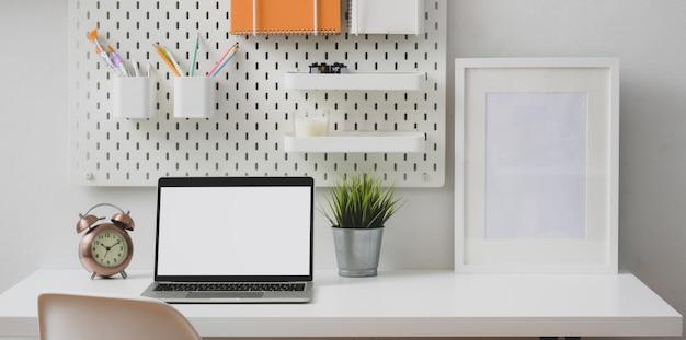 Moderner weißer arbeitsplatz mit offenem laptop-computer und modellrahmen mit stationärem