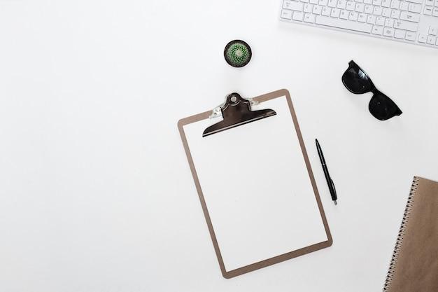 Moderner weißer blogger-tisch mit weißer tastatur, ordnertablett, sonnenbrille und kaktus