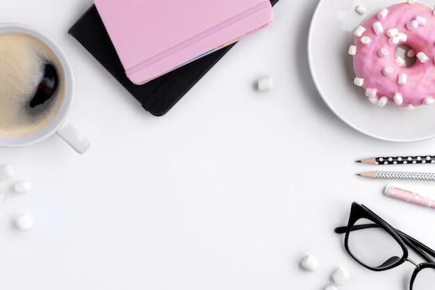 Moderner weißer home-office-schreibtisch mit notizblock, pensilien und tasse kaffee