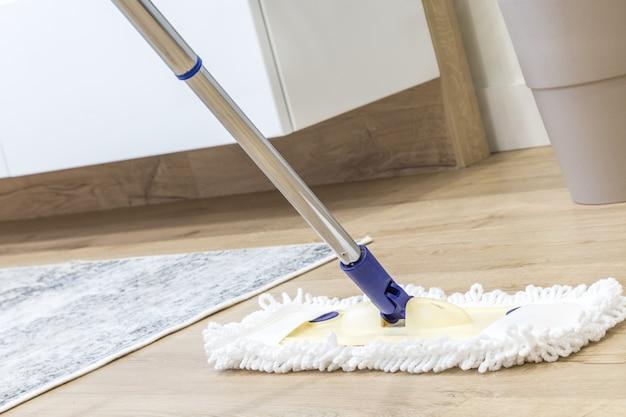 Moderner weißer mopp, der für das säubern eines bretterbodens verwendet wird