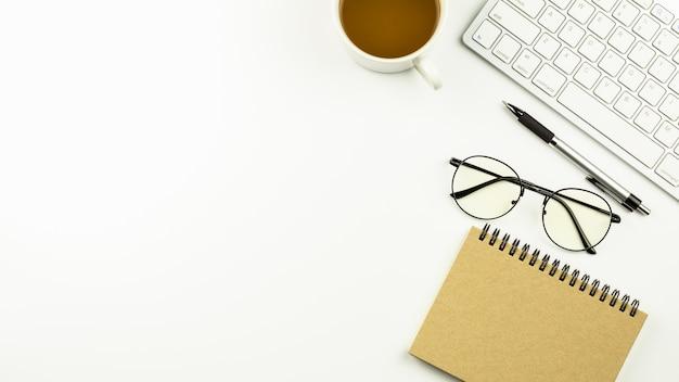 Moderner weißer schreibtisch mit einer computertastatur, einem stift, einem notizbuch und einem tasse kaffee