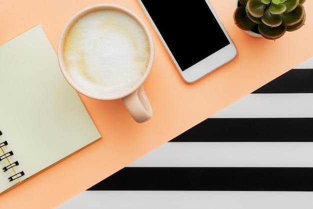 Moderner weißer schreibtisch-tisch mit smartphone und tasse kaffee. leere notizbuchseite zur eingabe des textes. draufsicht, flach liegen.
