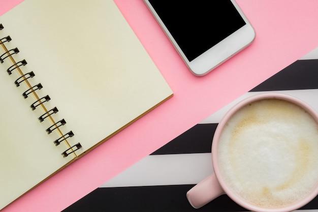 Moderner weißer schreibtisch-tisch mit smartphone und tasse kaffee. leere notizbuchseite zur eingabe des textes.