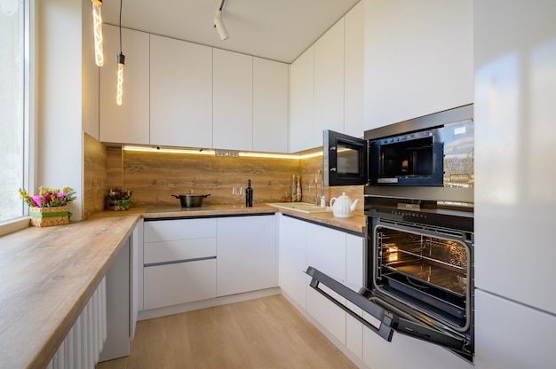Moderner weißer und beige hölzerner kücheninnenraum mit geöffnetem ofen
