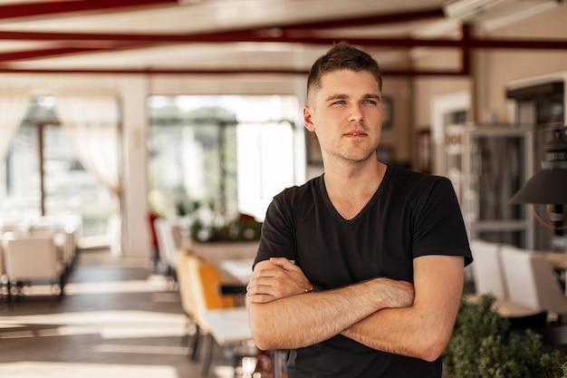 Modernes amerikanisches mannmodell eines jungen mannes mit einer stilvollen frisur in einem modischen schwarzen t-shirt, das im weinlesecafé stehend aufwirft