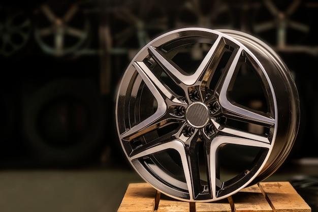 Modernes automobillegierungsrad aus aluminium auf einer schwarzen industrie. designer fashion räder für auto. nahaufnahme, schönes licht.