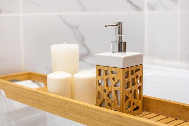 Modernes badezimmer mit holztisch und kerzen. seitenansicht der weißen marmorhintergrundwand