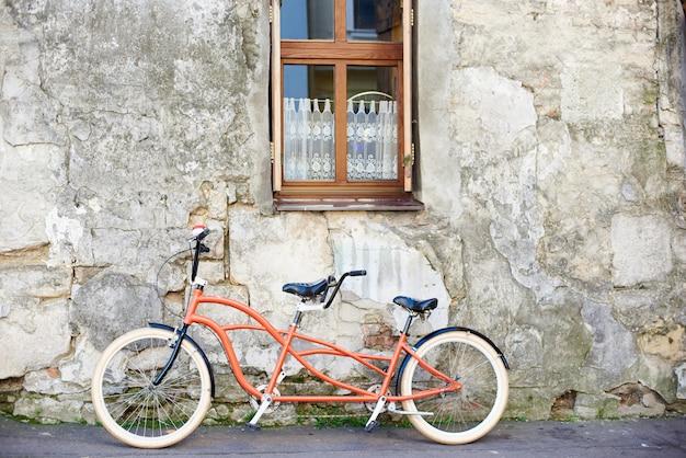 Modernes bequemes orangefarbenes tandem-doppelfahrrad mit weißen rädern lehnte an der alten verputzten rissigen vintage-hauswand mit spitzenvorhang auf kleinem sauberem fenster an hellem sonnigem sommertag.
