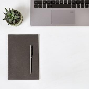 Modernes bildungskonzept, arbeitsplatz für studenten. arbeitsplatz. grauer computer, kleines saftiges, leeres notizbuch und stift auf tabelle. ansicht von oben. flach liegen. kopieren sie platz.