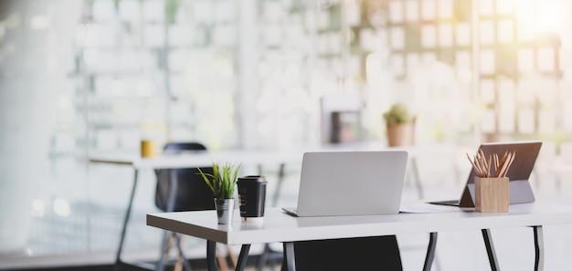 Modernes büro mit büroartikeln auf tabelle mit büroumgebung im hintergrund
