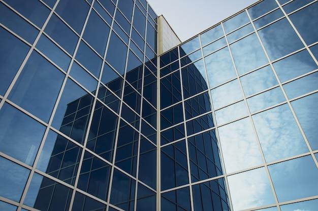 Modernes bürogebäude mit glasfenstern und blauem himmel. textur des hochhauses.
