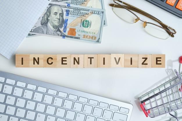 Modernes business-schlagwort - anreize schaffen. draufsicht auf tastatur und dollar mit holzklötzen. draufsicht.