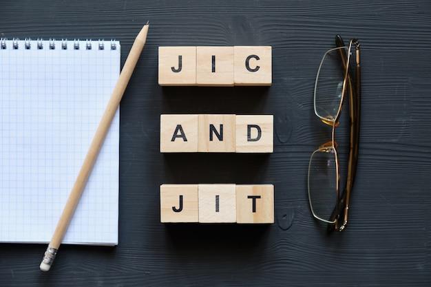 Modernes business-schlagwort - jic und jit. draufsicht auf brille und notizblock mit holzklötzen. draufsicht.