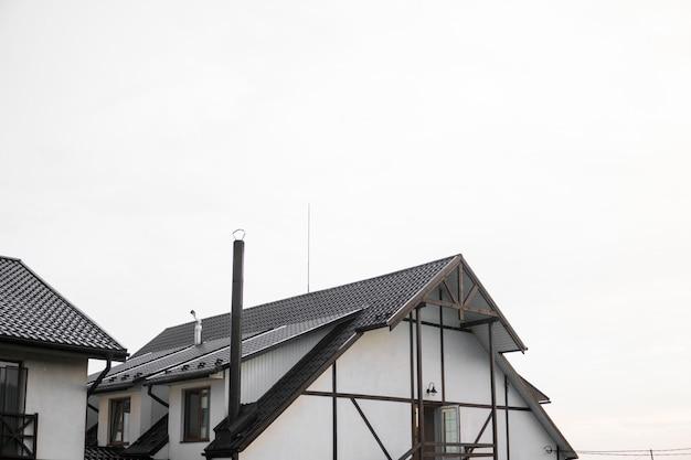Modernes dach mit pvc-beschichteten braunen metalldachplatten mit flieseneffekt gegen bewölkten himmel.