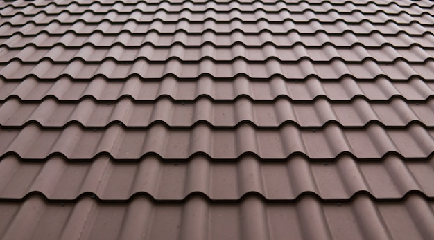 Modernes dach mit pvc-beschichteten braunen metalldachplatten mit ziegeleffekt.