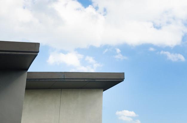 Modernes dachhaus mit einem blauen himmel im hintergrund. mit platz für ihren text.