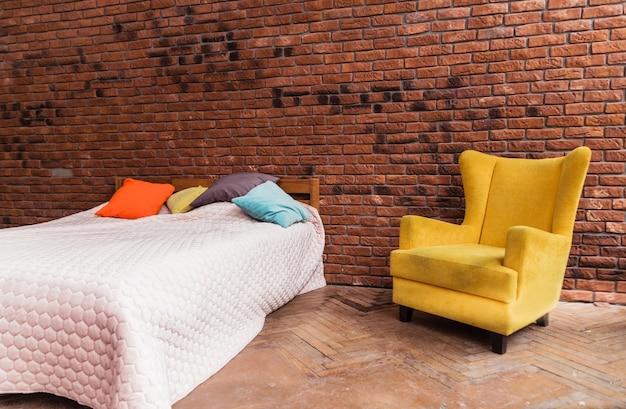 Modernes doppelbett und gelber sessel stehen gegen backsteinmauerhintergrund. horizontales foto
