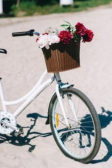 Modernes fahrrad mit korb mit blumen auf dem strand
